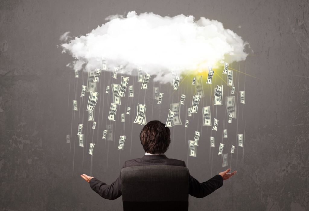 Business man in suit looking at cloud with falling money and sun